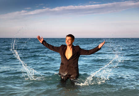 Smiling man in suit stands in sea and splash water at evening photo