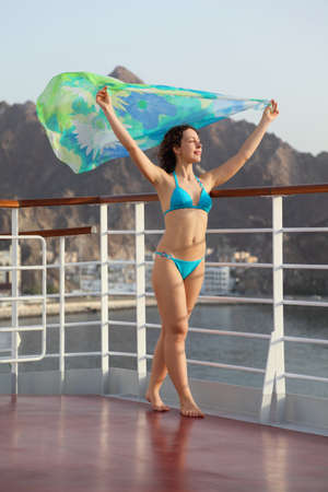 kerchief: beautiful woman with scarf is standing on deck of cruise ship.