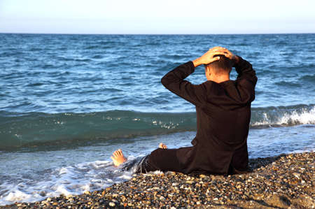 Beggarly barefooted man in suit sits back on stone coast and puts hand on head at evening photo