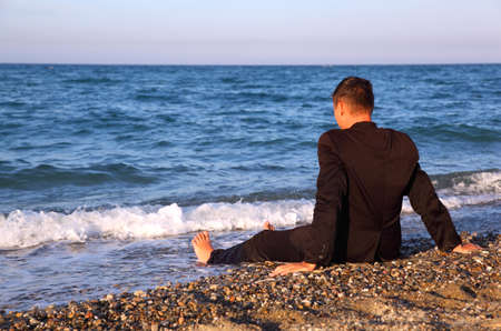 lonely man: Barefooted man in business suit sits back on stone coast at evening