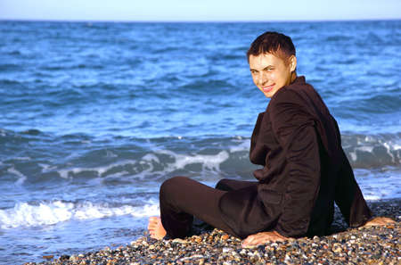Barefooted smiling man in suit sits on stone coast at evening photo