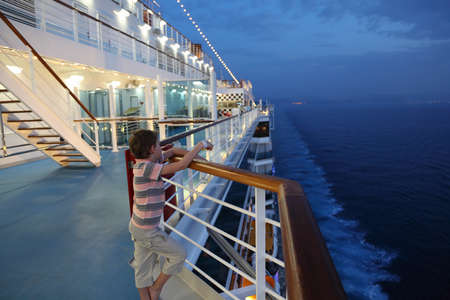 ship deck: little boy wearing shorts and striped shirt standing on deck of a ship and looking away