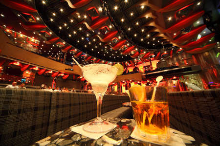adult cruise: big illuminated hall. coaches and tables. wineglass and glass with drinks in center of image. focus on top of wineglass. people in out of focus. wide angle. Editorial