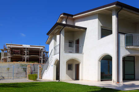 unfinished building: New finished white two-story house with garden, balcony and stairs to the right and unfinished building to the left
