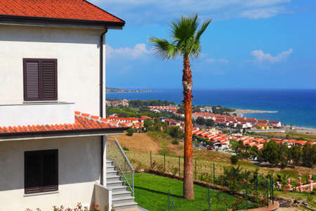 Big white two-story house with brown roof, palm trees and stairs on coast at city Stock Photo - 12512423