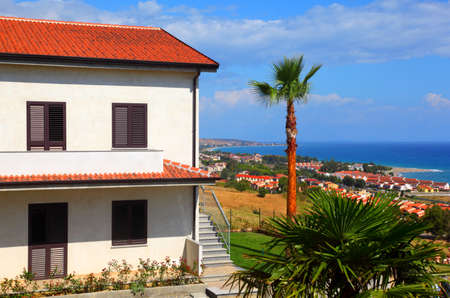 mandatoriccio: Big white two-story house with brown roof, palm trees and stairs on coast Editorial