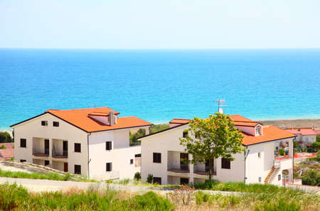 mandatoriccio: Building of new two-storey white houses with brown roofs and balcony on coast