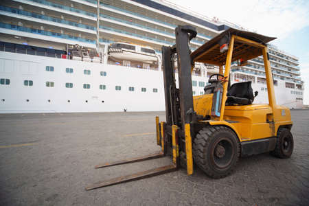 lifter: excavator in Qaboos port. focus on excavators wheel. cruise ship in out of focus.