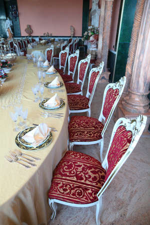mandatoriccio: Red chairs and big dinner table with empty dishes: plates with placemat, forks, knives and goblets