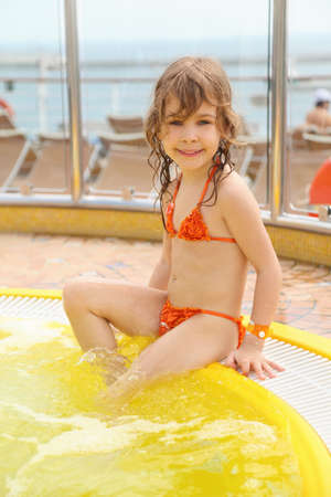 little girl wearing swimming suit sitting on edge of swimming pool photo