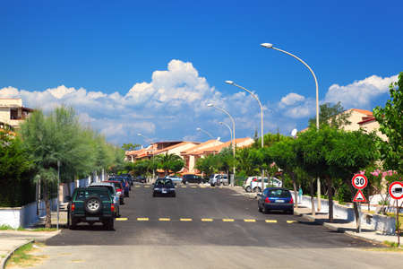 Cars drive on road and on the sidewalks are palm trees in residential area. Stock Photo - 12512503