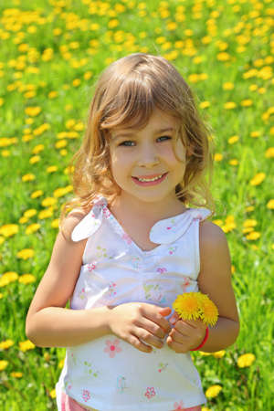 Little girl stands on  field and holds dandelions photo