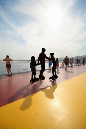 silhouette of adult man with two children on rollers on deck of cruise ship.