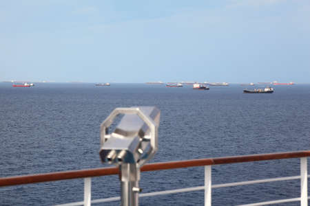 telescope on deck of cruise ship in out of focus. many ships far away.