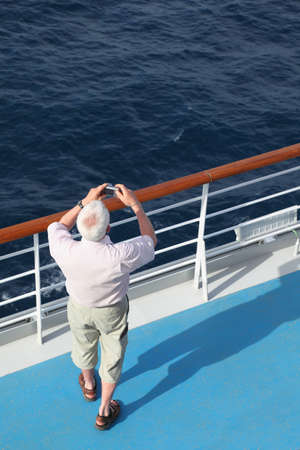 man with compact photo camera standing on deck of cruise ship and shooting. photo