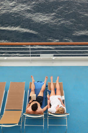 cruise travel: couple: man and woman both relaxing on chaise longues.