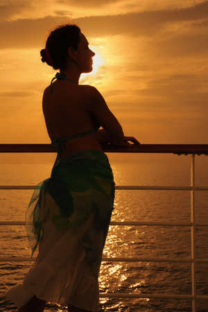 beautiful woman standing on deck of cruise ship and looking away. evening. Stock Photo