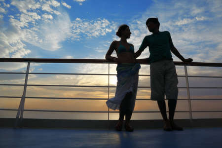 man and woman on deck of cruise ship. man looking at woman and woman looking at man. Stock Photo