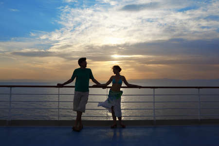 adult cruise: man and woman standing on deck of cruise ship. woman looking at man and man looking at woman.