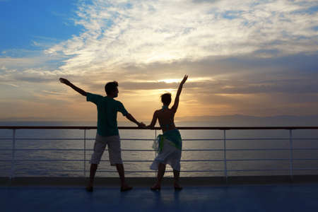 man and woman standing on deck of cruise ship and looking away photo