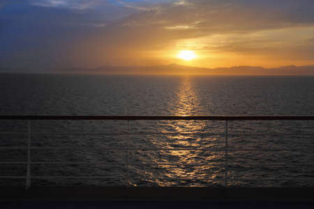 beautiful sunset above water. view from deck of cruise ship. rail in out of focus. photo