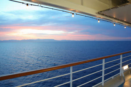 ship deck: beautiful view from deck of cruise ship. sunset. row of lamps. Stock Photo
