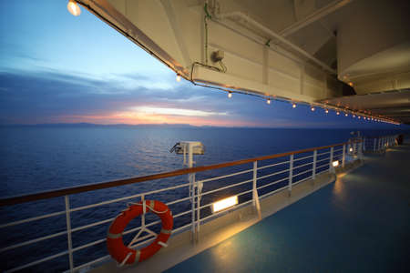 ship deck: beautiful view from deck of cruise ship. sunset. row of lamps. lifebuoy.
