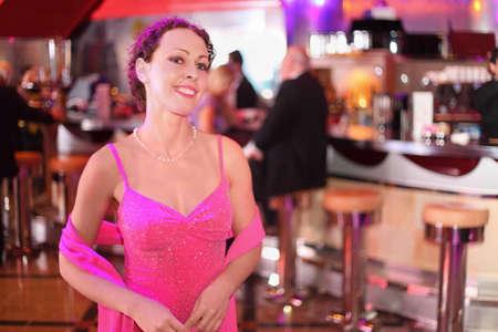 beautiful smiling woman wearing evening dress standing in bar. photo