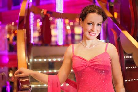 beautiful smiling woman wearing evening dress in illuminated hall. photo