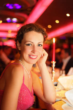 candle light dinner: smiling beautiful woman wearing evening dress is sitting in illuminated hall. Stock Photo