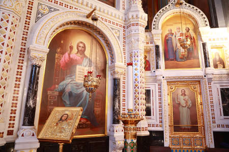 Icons and stand for candles near painting in arch inside Cathedral of Christ the Saviour in Moscow, Russia Sajtókép