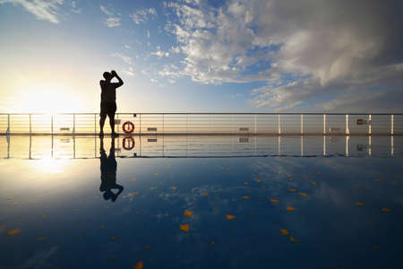 photo shooting: man with compact photo camera shooting morning sky from deck of cruise ship. reflection in deck.