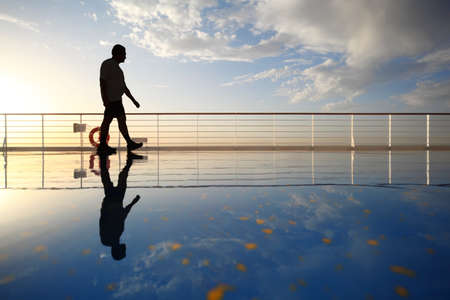 adult cruise: silhouette of old man walking throught deck of cruise ship. morning golden sun shining. reflection in deck.
