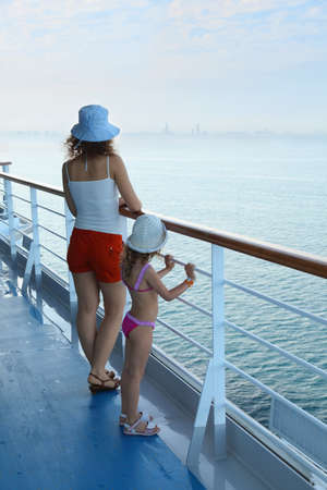 woman and her daughter standing on deck of cruise ship and looking away photo