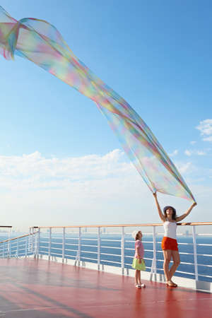 woman with big scarf standing on deck of cruise ship. little girl looking at kerchief photo