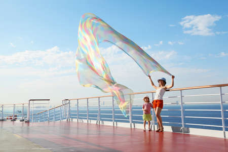 chaise longue: woman with kerchief standing on deck of cruise ship. her daughter looking at kerchief