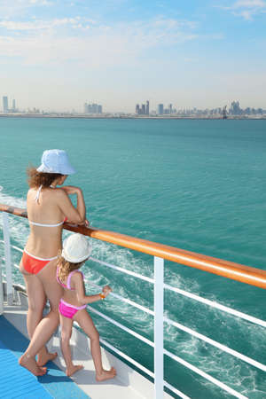 adult cruise: woman and her daughter standing on deck of cruise ship and looking at water.
