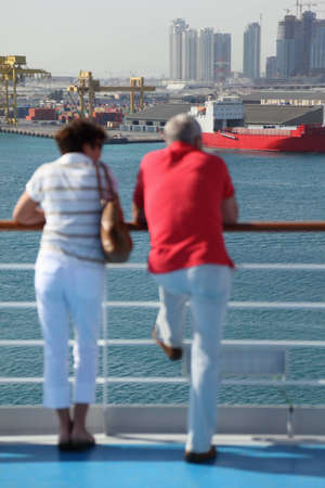 moorings: man and woman standing on deck of cruise ship and looking at port. man and woman in out of focus. Stock Photo
