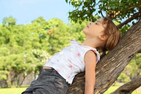 pacification: Little girl lies on caudex of tree