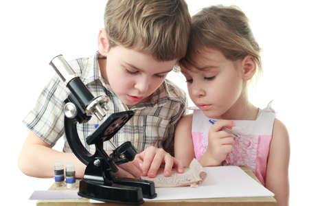 Curious little boy and girl draw diagram near black microscope photo