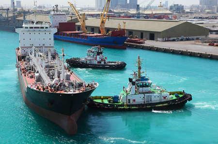 autobotte: Due piccole imbarcazioni ancorata alla nave in porto industriale a giornata di sole Archivio Fotografico