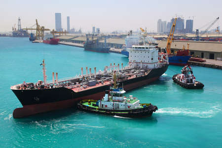 Two boats docked to industrial ship in port sail to sea at sunny day  in Abu Dhabi photo