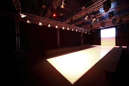 modelo en pasarela: Vista lateral de brillaban podio antes de comienzo de pantalla de moda Editorial