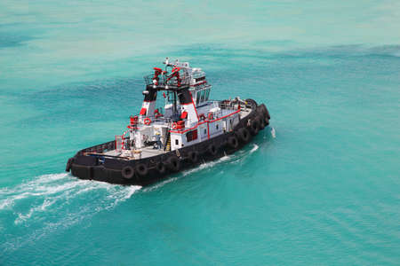 tug boat: Pilot on little fire pusher tug drift through the sea at day