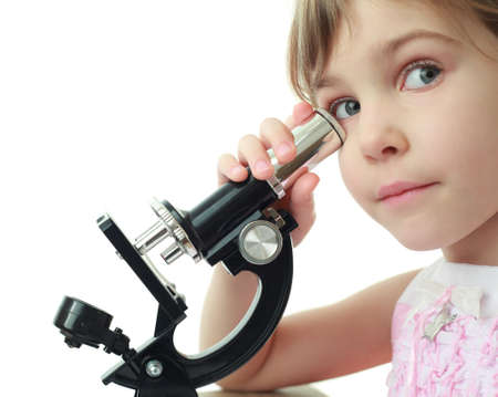 experiment: Portrait of cute little girl leaned against eye to microscope Stock Photo