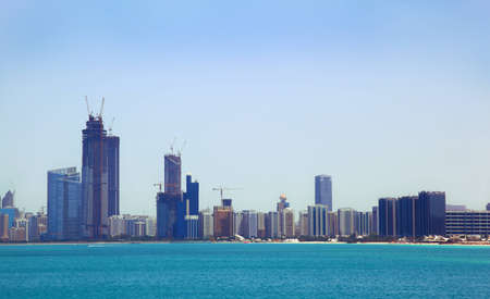 shore line: The view from the sea of the buildings and skyscrapers in Abu Dhabi downtown.