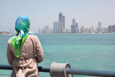 lejos: Chica en el pa�uelo azul de pie en el barco y relojes de los edificios y el paseo mar�timo de Abu Dhabi.