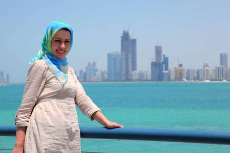 Smiling girl in blue kerchief standing on the ship against skyline of Abu Dhabi buildings