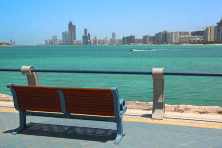 abu dhabi: Red bench overlooking Abu Dhabi buildings before the sea at sunny day Stock Photo