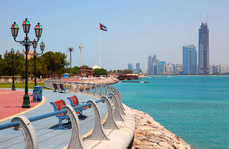 Red benches in park on the seafront against the backdrop of Abu Dhabi buildings